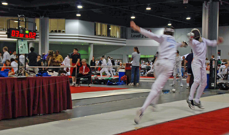 Sam Hayden (right) scores on a stop hit against the fleche in Division III Men's Epee.