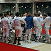 Division III Men's Epee fencers gather to receive instructions from the referee at the start of the direct elimination round.