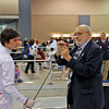 Referee David Micahnik checks Jake Mezey's epee in the Youth-14 Men's Epee.