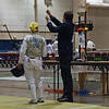 The referee tests Bettie Graham's foil in the Veteran-70+ Women's Foil.