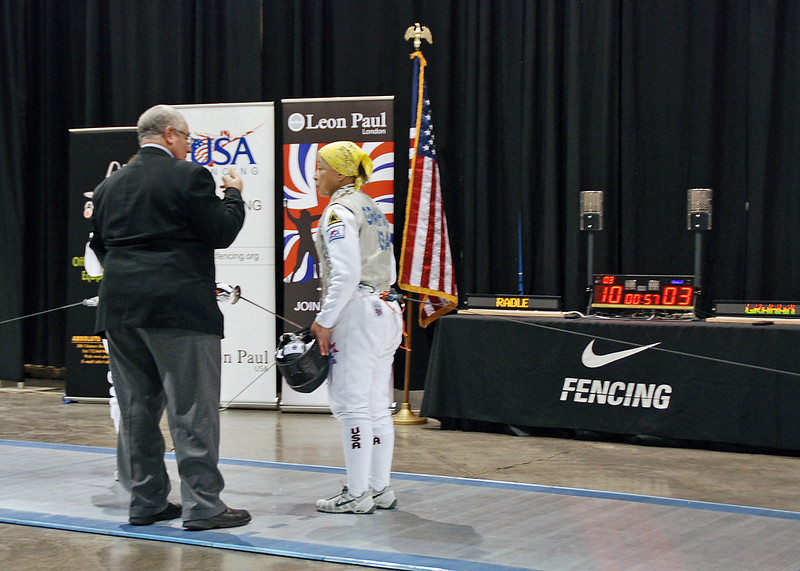 The referee checks the fencers in the Bettie Graham vs. Catherine Radle quarter-final bout of the Veteran-70+ Women's Foil.