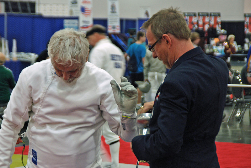 Referee Gary Van der Wege checks the epee of Kaz Campe in the semi-final bout of Veteran-70+ Men's Epee.