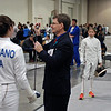 Referee Ray Gordon checks the epee of the competitors in Elise King's Youth-12 Women's Epee bout.