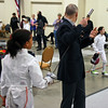 The referee checks Olivia Castel's epee in the Youth-12 Women's Epee.
