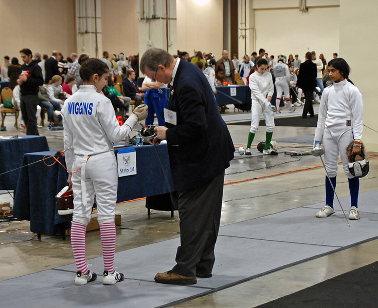 The referee inspects Elizabeth Wiggins equipment in the Youth-14 Women's Epee.