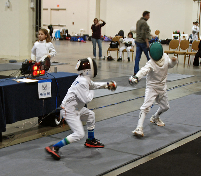 Bryce Knight (left) scores a touch on his opponent in the Youth-10 Men's Epee.
