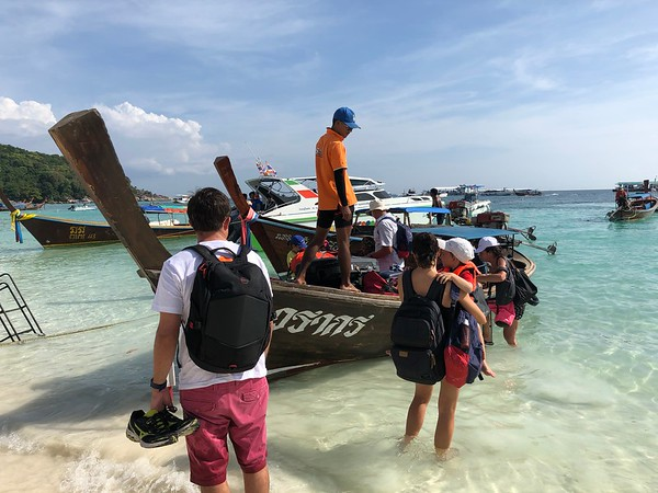 Passengers boarding a longtail boat to the waiting ferry