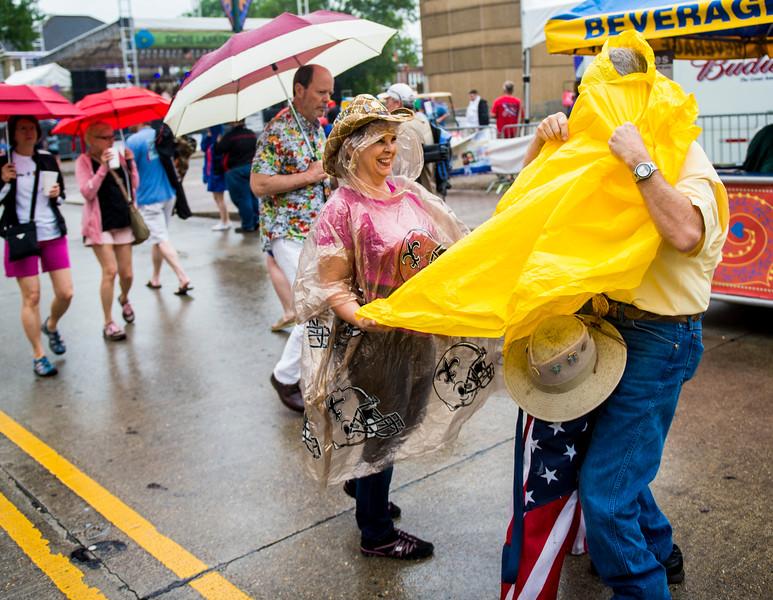 Cyndi Faulk assists her husband Charles Faulk put on a rain poncho as rains begin during Festival International de Louisiane in downtown Lafayette, LA, Friday, April 24,2015.