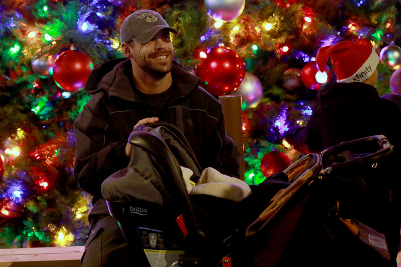 Cole Dixon sits next to the Christmas tree with his five-month-old daughter Nora Dixon at the Festival of Lights Lighting Ceremony in Loveland, Colo. on Nov. 30, 2018.<br /> Photo by Taelyn Livingston/ Loveland Reporter-Herald
