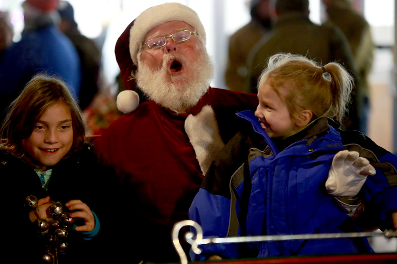 Selena Gauger, 8, and Neriah Jimenez, 4, sit with Santa, sometimes known as John Perrine, during the Festival of Lights Lighting Ceremony in Loveland, Colo. on Nov. 30, 2018.<br /> Photo by Taelyn Livingston/ Loveland Reporter-Herald
