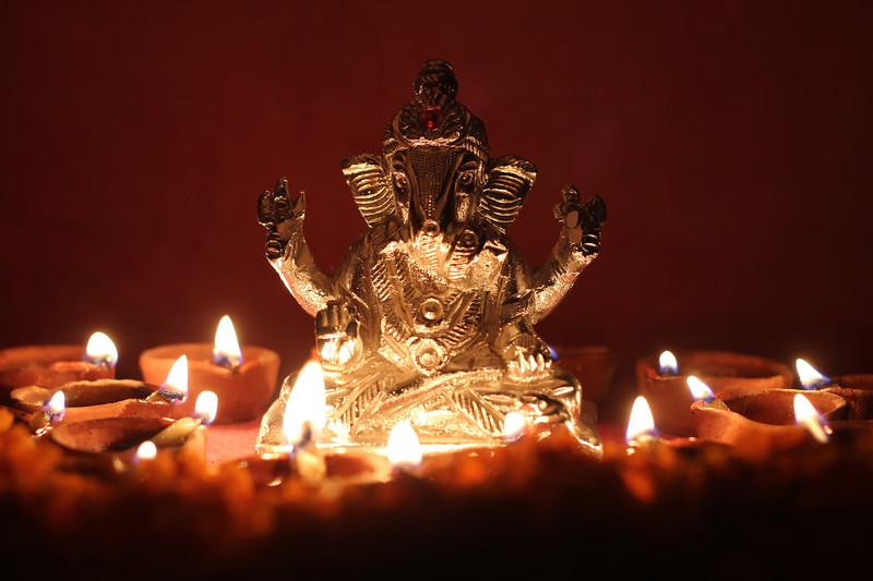 Ganesh idol surrounding with oil lamp, festival season