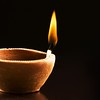 Single Burning Flame in an Earthen Lamp on a Black Background