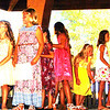 Debbie Blank | The Herald-Tribune<br /> Royalty pageant master of ceremonies Dylan Flannery (from left) chats with Hilary Ziegler while other second-grade Miss Apple Dumpling candidates file off the stage: Megan Townsley, Addison McGuire, Kathryn Mack, Alexia Lykins, Ivy Lewis (hidden from view), Amari Lakins, Maggie Jelinek, Charlotte Harmeyer and Molly Gesell.