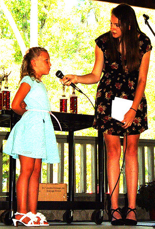 Debbie Blank | The Herald-Tribune<br /> So the judges can evaluate poise, personality and appearance, mistress of ceremonies Kiley Cline (right) asks Miss Apple Blossom contender Harper Buckley a question during the royalty pageant.