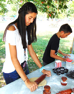Valentina Aguila (left), 11, Batesville, and her brother, Alex, 8, imagine what it was like to make pie crusts and biscuits without the use of machines at the Batesville Memorial Public Library Interactive Pioneer Living Exhibit.