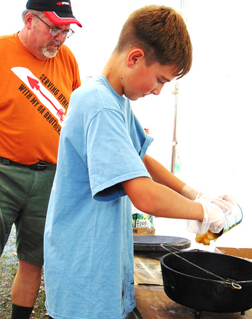 Boy Scout Troop 634 member Holten Harrison (right), 12, Batesville, gets going on a new batch of apple cobbler under the watchful eyes of Scoutmaster Mark Hamer.