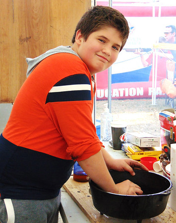 Liam Livers, 13, Oldenburg, of Boy Scout Troop 634 smiles during dishwashing duty.