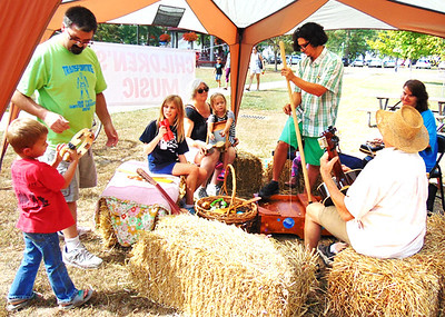 The Batesville-based Lucky Ducks band brings the joy of music to children who could try a variety of instruments at the fest. Performing a song are (from left) Carter, 4; dad Joey and Serenity Feldmann, 9; Jan, Zoe, 5 and Rudy Eckstein; Jeff McKinley; and Debbie Brown.