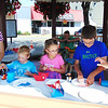 Diane Raver | The Herald-Tribune<br /> Michelle Luhring (from right), a Batesville Memorial Public Library employee, helps Robert, Alaina, Matthew and Amanda Jensen, Wyoming, make boats for the Batesville Regatta.