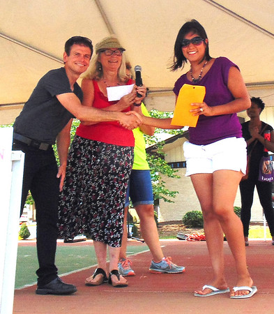 Diane Raver | The Herald-Tribune<br /> Laura Conejo (from right), who placed first in the amateur division of the Salsa Cook-off, is congratulated by Food and Growers Association members Mary Meyer and Michael Hood.
