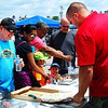 Debbie Blank | The Herald-Tribune<br /> Sean Townsley (left), Batesville Main Street Promotional Committee chair, who headed up Batesville Bash, gets a free sample of pizza grilled on a Big Green Egg at the Gillman Do It Best Home Center booth. He is being served by Batesville manager Kyle Higham.