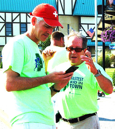 Debbie Blank | The Herald-Tribune<br /> Some finishes were so close that volunteers Joe Raver (left) and Dogger Dickey had to check cellphone videos.