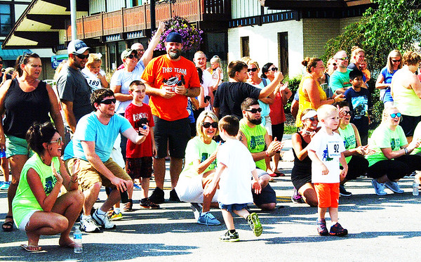 Debbie Blank | The Herald-Tribune<br /> Parents and friends near the finish line coax the youngest entrants to try their hardest.