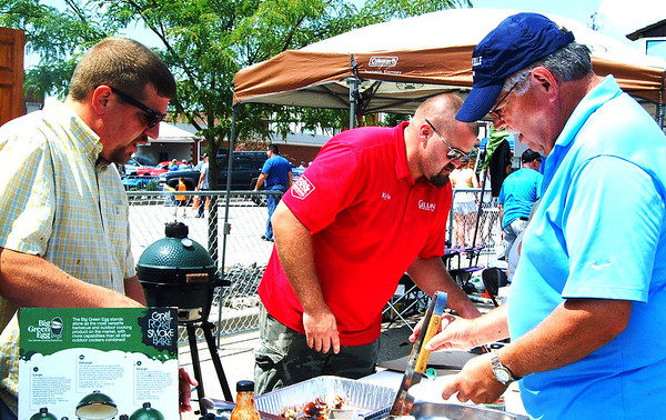 Debbie Blank | The Herald-Tribune<br /> Gillman Do It Best Home Center chief operations officer Curtis Gillman (from left) and Batesville manager Kyle Higham serve samples of pizza and brats and sausages prepared by Langen Meats and made in a Big Green Egg to attendees, including Mike Vonderheide, Batesville.