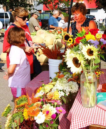 Debbie Blank | The Herald-Tribune<br /> Gina Grote, Batesville, and daughter Laura buy sunflowers from Sharon Steinfort, Batesville, at a Batesville Farmers' Market stand that offers a fantastic variety.