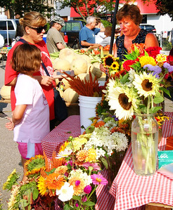 Debbie Blank | The Herald-Tribune Gina Grote, Batesville, and daughter Laura buy sunflowers from Sharon Steinfort, Batesville, at a Batesville Farmers' Market stand that offers a fantastic variety.