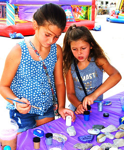 "Debbie Blank | The Herald-Tribune Grace Gutzwiller (left), 10, and sister Mikaela, 8, Batesville, painted Kindness Matters rocks in the Children's Health Care Kids Zone. Each rock has a message underneath. ""We're going to leave them around town. Everyone will look for them and rehide them,"" explained Children's Health Care Batesville/Greensburg business manager Brenda Skinner, who was in charge of that area."