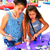 "Debbie Blank | The Herald-Tribune<br /> Grace Gutzwiller (left), 10, and sister Mikaela, 8, Batesville, painted Kindness Matters rocks in the Children's Health Care Kids Zone. Each rock has a message underneath. ""We're going to leave them around town. Everyone will look for them and rehide them,"" explained Children's Health Care Batesville/Greensburg business manager Brenda Skinner, who was in charge of that area."