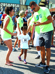 Debbie Blank | The Herald-Tribune Fastest Kid in Town volunteers Amy Watson (left) and J.B. Showalter (right) get ready to give a medal to the swiftest 5-year-old girl, Sophia Schuerman.