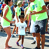 Debbie Blank | The Herald-Tribune<br /> Fastest Kid in Town volunteers Amy Watson (left) and J.B. Showalter (right) get ready to give a medal to the swiftest 5-year-old girl, Sophia Schuerman.