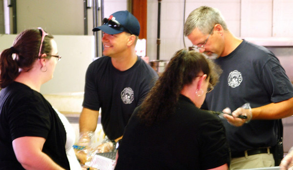 Christopher Aune | The Herald-Tribune<br /> Firefighters John Howery (left) and Matt Hertel, captain of Ladder Truck 47; serve dinner to fish fry customers Friday, July 11.