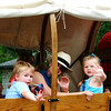 Christopher Aune | The Herald-Tribune<br /> Wagon riders Henry Candelot (from left), grandmother Marcia Kurtz, Batesville, and Stella Kurtz wave at spectators during the parade Saturday.