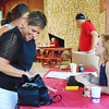 Debbie Blank | The Herald-Tribune<br /> Susan Dreyer (left) and daughter GiGi (behind her) pay volunteer Sammie Hardebeck for raffle tickets.