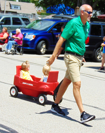 Debbie Blank | The Herald-Tribune<br /> Batesville Middle School teacher, Batesville High School basketball coach and real estate agent Aaron Garrett accompanies two toddlers in the parade.