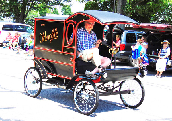 Debbie Blank | The Herald-Tribune<br /> Spectators expected to view firetrucks at the procession, but a pristine 1904 Oldsmobile was a surprise.