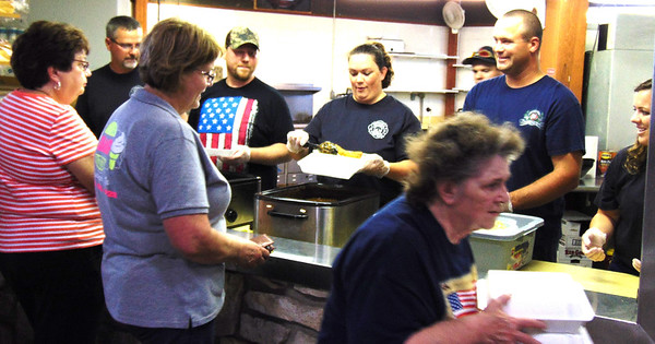 Debbie Blank | The Herald-Tribune<br /> Batesville firefighter Matt Hertel (from left behind counter), volunteer John Schutte, firefighters Natasha and Trevor Fischmer and Ben Eisert and EMT Hannah Putnam serve fried cod dinners, which included baked beans, cole slaw, chips and a drink, Friday night. In the back of the pavilion kitchen, volunteer Nancy Fischmer was cutting up onions for green beans the next day.