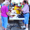 "Debbie Blank | The Herald-Tribune<br /> Anna Mae and Ambrose Nobbe (from left) pay volunteer Herb Hoff for their fried fish suppers. The couple attended because ""we're going to support the fire department and we like to eat out,"" she reported."