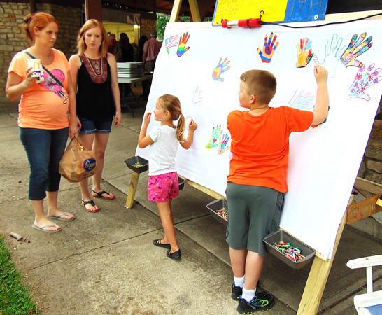 Debbie Blank | The Herald-Tribune<br /> Evan Burdette (from right), 7, Sunman, and Kinley Lanham, 5, Batesville, color hands on an artwork as fest volunteer Sammie Hardebeck and mom Karen Lanham, Batesville, watch. Christian art missionary Paul Wislotski, Largo, Florida, who oversaw the creation, urged Batesville leaders to send the art to the family of New York Police Department Officer Miosotis Familia, who was killed July 6, leaving behind three children.