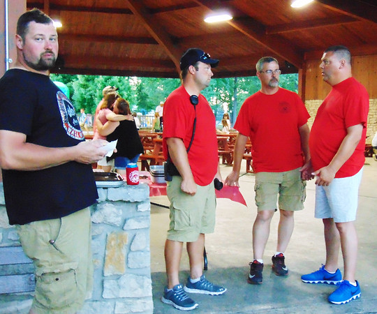 """Debbie Blank   The Herald-Tribune<br /> Batesville Fire & Rescue Chief Todd Schutte (from right), Capt. Matt Hertel and President Casey Schomber assess the fest Saturday night while Ben Dorrel, Batesville, munches on a burger in the pavilion. Schomber said beforehand, """"We put a lot of time and effort into this. We began preparing for this year's fest at the end of last year's to make sure everything works out well. We try to have things for adults and children, so it's family-oriented."""""""