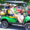 Debbie Blank | The Herald-Tribune<br /> A golf cart was a breezy way to take part in the procession.