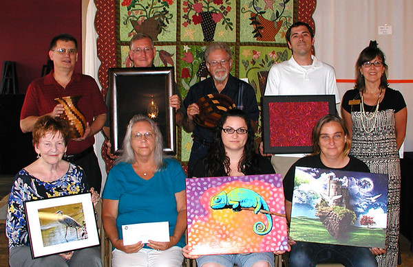 ART SHOW coordinator Connie Rozman (top row at right, then counterclockwise) congratulates winners Peter Hertel, Paul Borchelt, Jim Hunter, William Jones, Janet Smith, Carmen Nunlist (with her quilt behind the group), Heather Paul and Jaime Mustaine.