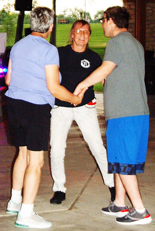 Debbie Blank | The Herald-Tribune<br /> Three share a sunset dance June 21 in the pavilion.