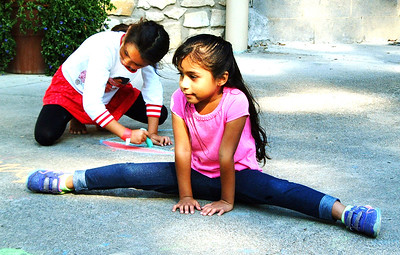 Debbie Blank | The Herald-Tribune Ariana Cisneros Hernandez, 4, Sunman, does the splits while Sophia Hillenbrand, 5, Batesville, makes a chalk drawing.