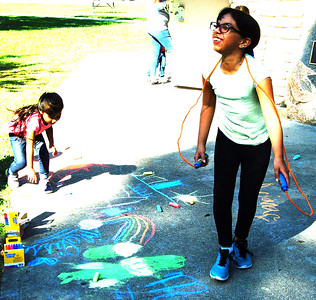 Debbie Blank | The Herald-Tribune Ariana, 4, creates a chalk drawing while sister Melissa Cisneros Hernandez, 9, Sunman, jumps rope outside the pavilion in the children's activities area.