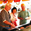 Debbie Blank | The Herald-Tribune<br /> Oldenburg residents (from left) John Lamping, Diana Enneking and Bill Gehring grill hot dogs, brats and metts in the sandwich stand area.