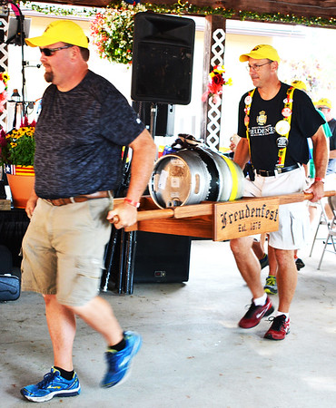 Debbie Blank | The Herald-Tribune<br /> Freudenfest Committee members Greg Struewing (left) and Troy Ilderton bring the first keg to the opening ceremony to be tapped to get the merriment going.
